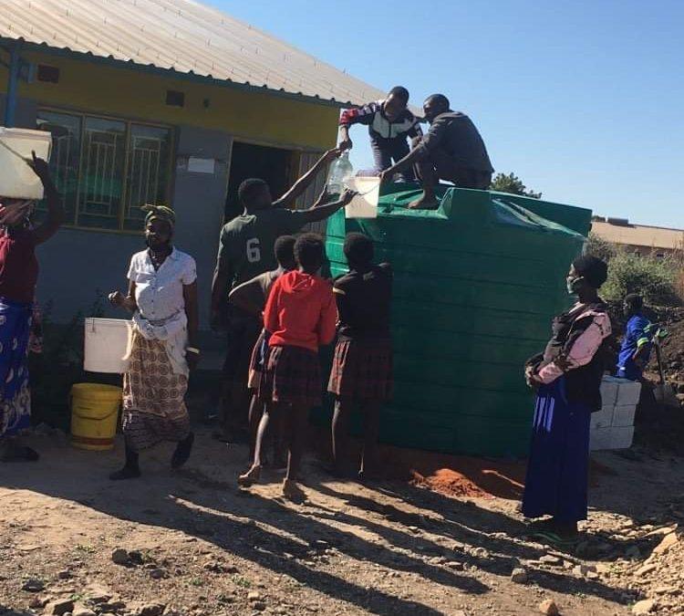 Community members help fill water tank.
